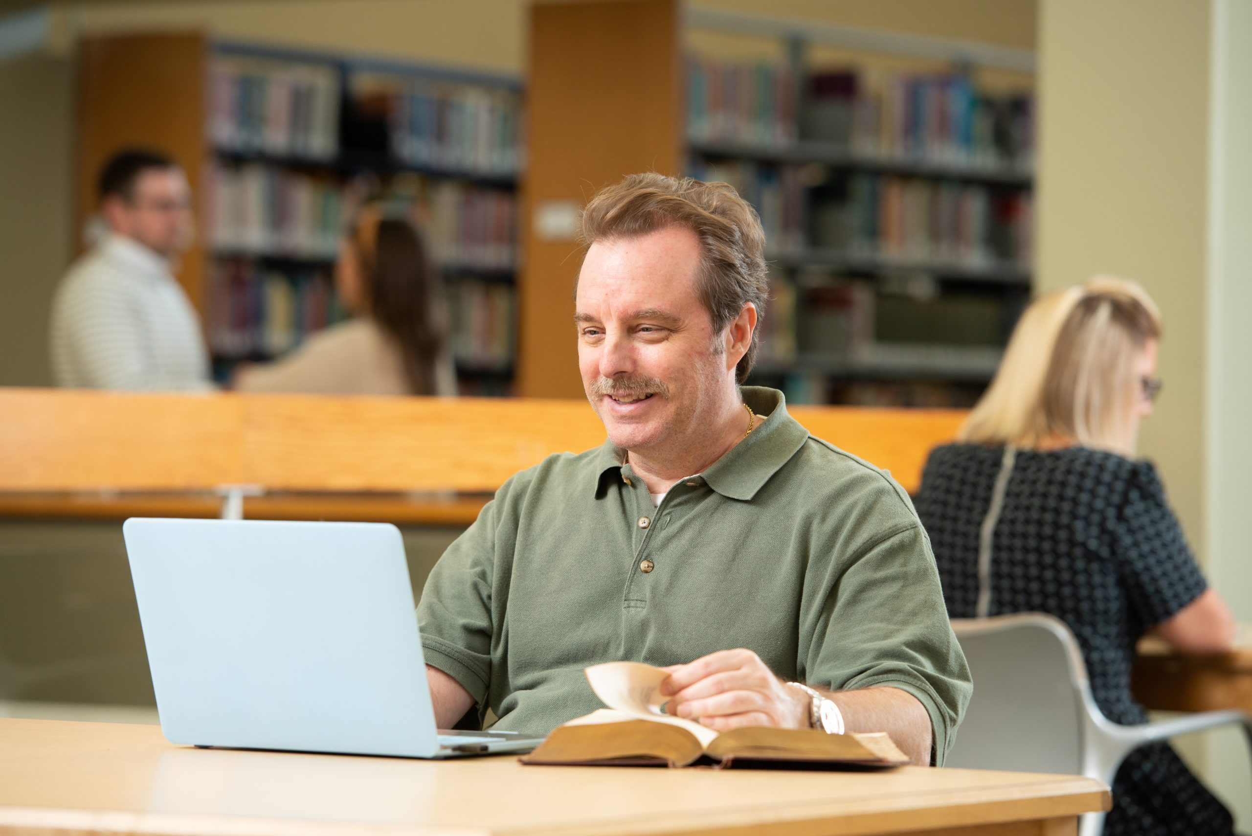 man in library using a laptop