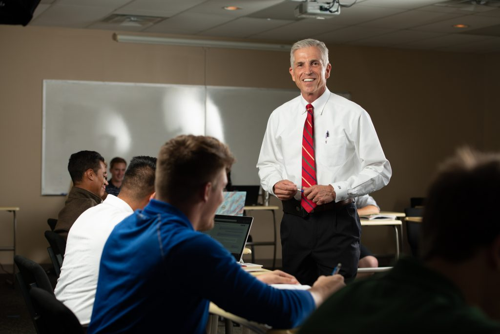 Male Professor smiling at his students