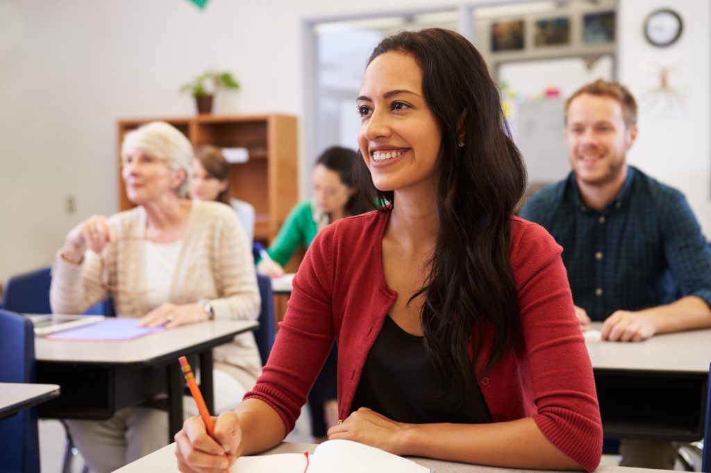 woman taking notes and smiling