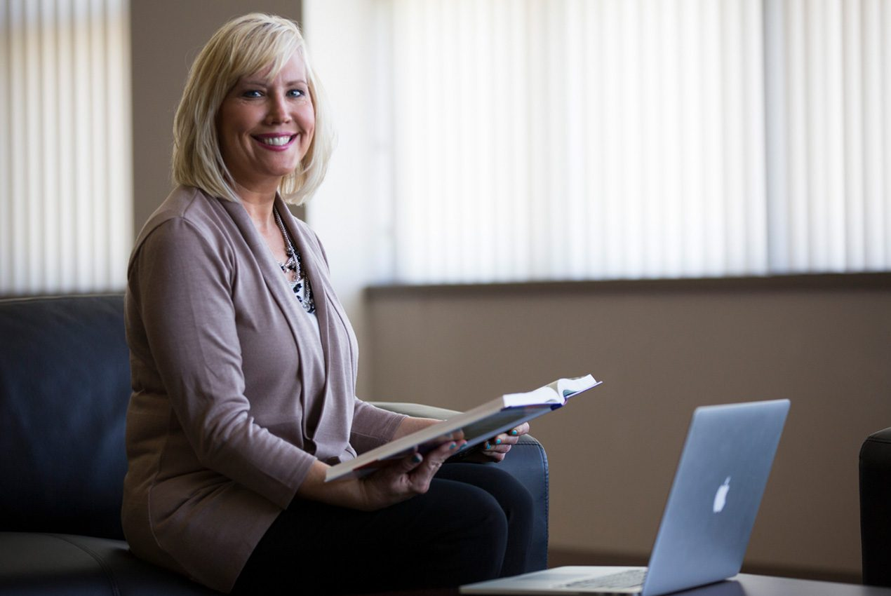 woman holding book in front of lap top